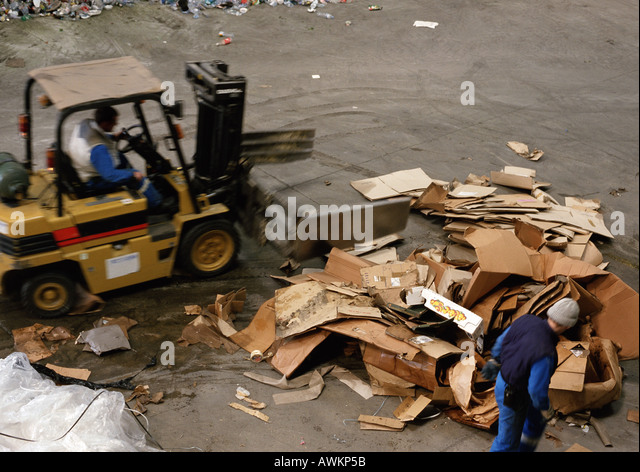 Workers moving large pile of cardboard boxes - Stock Image