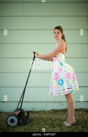 Portrait of young woman in 1950s dress with an old push lawnmower - Stock Image