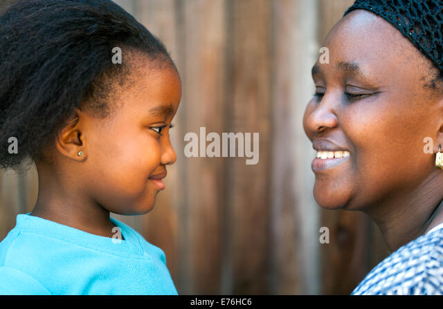 Close up portrait of African mother and daughter looking at each other. - Stock Image