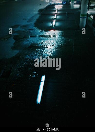 Strip lights reflecting in a puddle on a multi storey car park floor - Stock Image