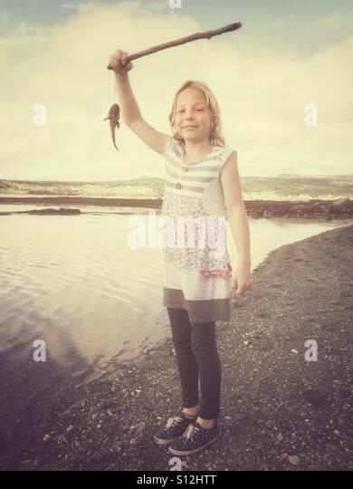 A girl having just caught a fish with a homemade fishing rod. - Stock Image