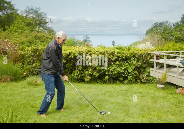 Portrait of senior man, practising golf swing - Stock Image