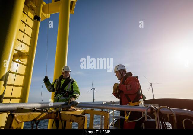 Engineers about to climb wind turbine on offshore wind farm - Stock Image