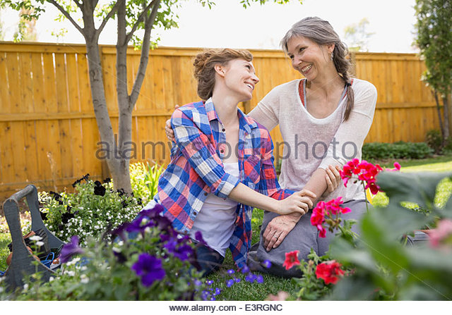 Affectionate mother and daughter planting flowers in garden - Stock Image