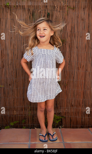 Wind blowing young girl in sundress - Stock Image
