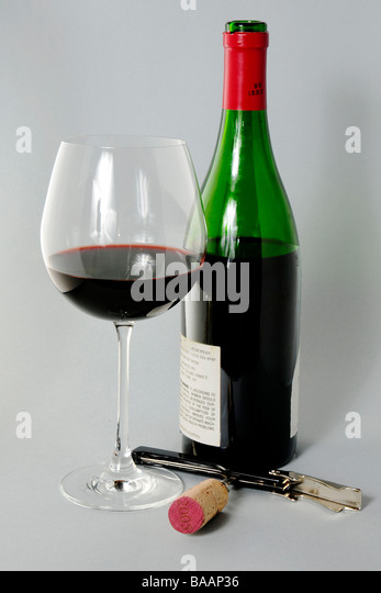 Bottle of red wine with half full glass and corkscrew with cork - Stock Image