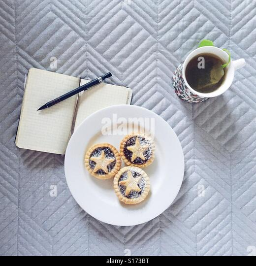 Mince pies on a plate, herbal tea and a notebook with pencil - Stock-Bilder
