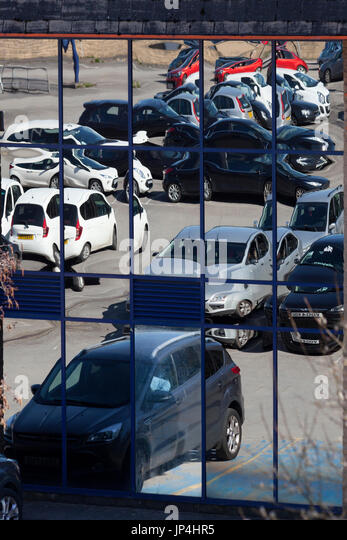 Car park reflected in store window, Halifax, West Yorkshire - Stock Image