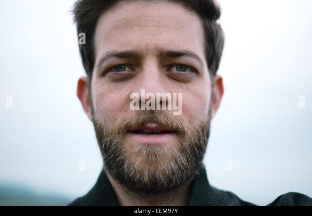 Man with beard looking at camera - Stock Image