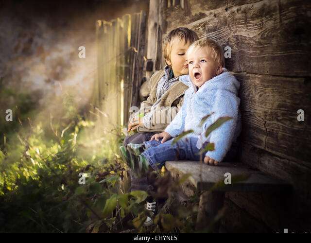 Two brothers sitting on a wall having fun - Stock Image