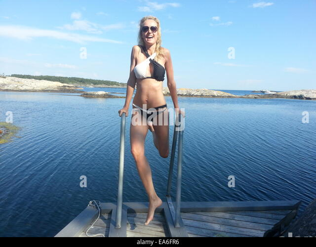 Woman on jetty ready to go swimming - Stock Image