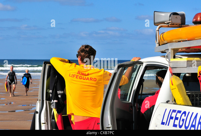 Mature surfers walks across Croyde Beach after surfing with an on- duty RNLI life guard looking on . - Stock Image