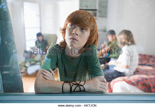 Boy looking out of window - Stock Image