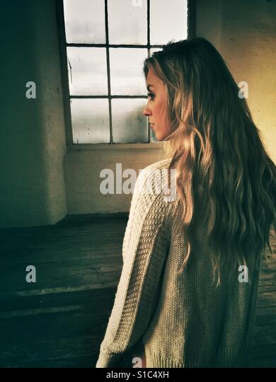 Rear view of a young blond woman looking away - Stock-Bilder