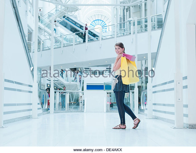 Teenage girl carrying shopping bags in mall - Stock Image