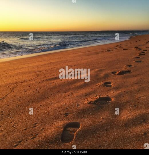 Sunset on a beach in Portugal with foot prints in the sand leading of in to the horizon. - Stock-Bilder