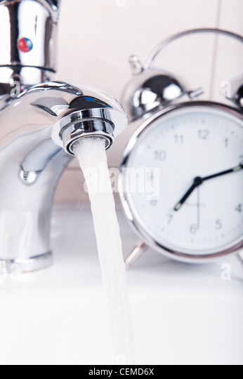 Modern chrome faucet and alarm clock  Wasting time and water concept    Stock Image. Clock Bathroom Stock Photos  amp  Clock Bathroom Stock Images   Alamy