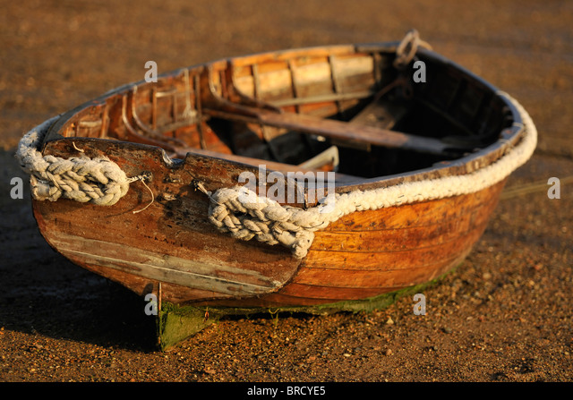 A traditional wooden rowing boat on shingle. - Stock Image