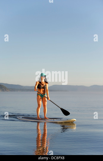 A woman, Stand Up Paddleboarding (SUP) on Lake Tahoe in the early morning on calm glassy waters, CA. - Stock Image