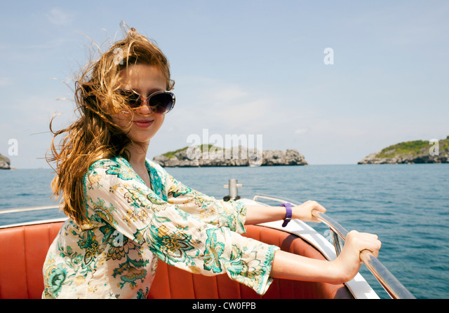 Smiling woman riding on boat - Stock Image