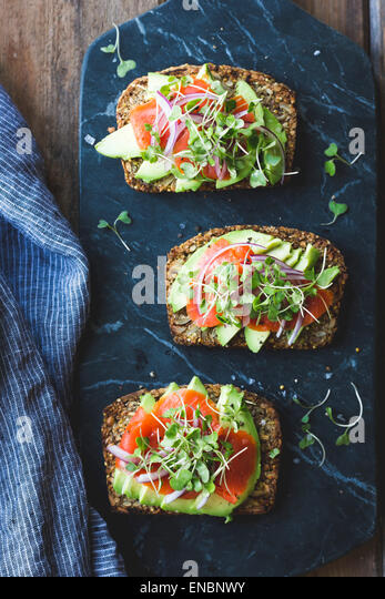 A Gluten-Free Vegan Nut and Seed Bread with avocado salad topping - Stock Image