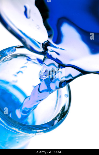 Blue colored liquid pouring from beaker into laboratory glass flask. - Stock Image