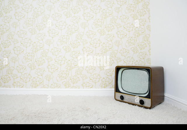 Retro television in corner of room with patterned wallpaper - Stock Image