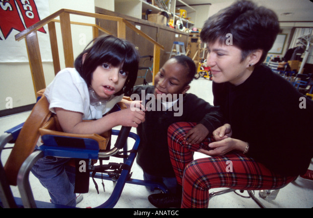 New Jersey East Orange Cerebral Palsy Center disabled student female therapist walker Black boy - Stock Image