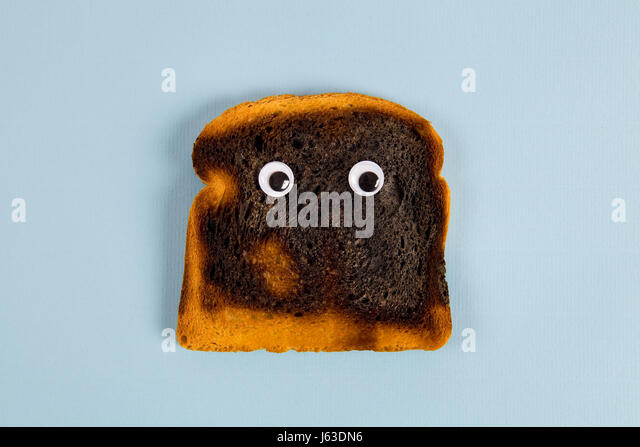 a quirky burned soft bread with eye's doll Still life and minimal photography - Stock Image