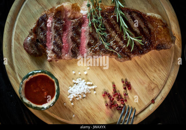 Sliced medium rare grilled steak on rustic cutting board with rosemary and spices , dark rustic metal background, - Stock Image