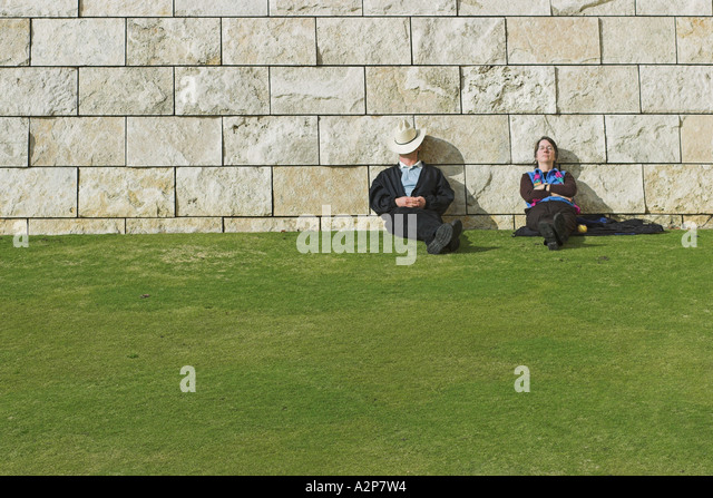 A man and a woman sleeping on the grass at the J. Paul Getty Museum in Los Angeles, CA. - Stock Image