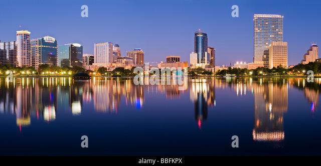 Glowing nighttime downtown skyline of Orlando Florida reflects in Lake Eola - Stock Image