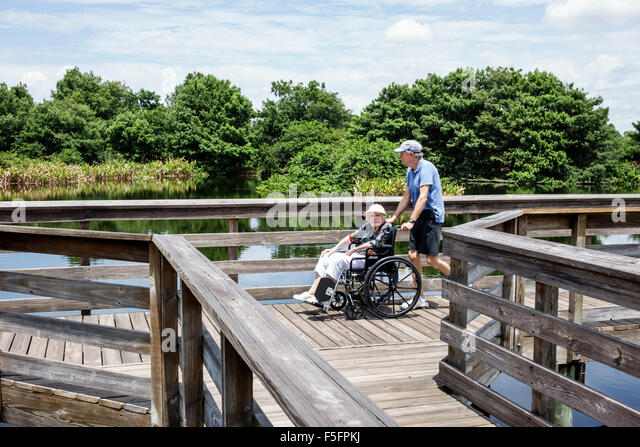 Florida Delray Beach Wakodahatchee Wetlands nature preserve raised boardwalk man senior woman wheelchair elderly - Stock Image