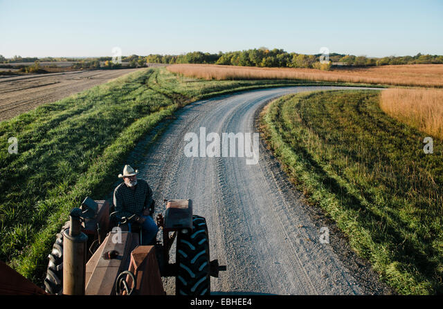 High angle view of senior male farmer driving tractor on rural road, Plattsburg, Missouri, USA - Stock Image