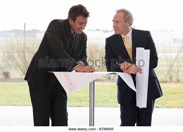 Two businessmen looking at blueprints in an office building - Stock Image