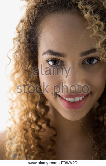 Close up of smiling woman with curly hair - Stock Image
