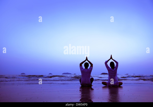 family yoga on the beach at sunset - Stock Image