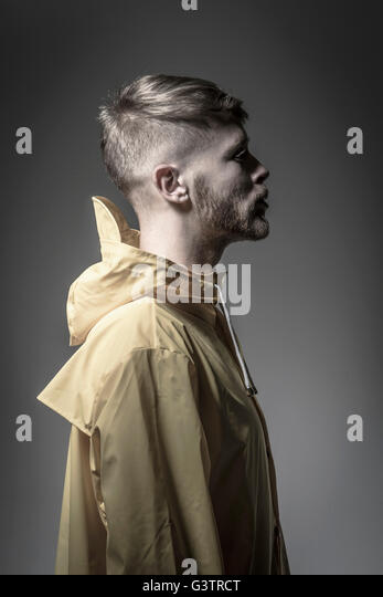 Studio portrait of a bearded young man in a yellow wind cheater. - Stock Image