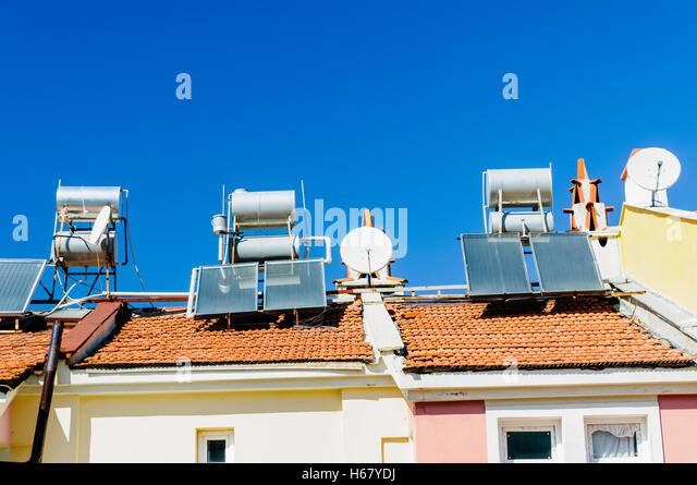 Solar water heaters and satellite dishes on the roof of a building in a hot climate. - Stock Image