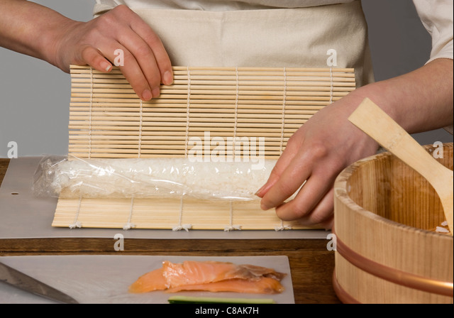 Cook rolling the rice in a mat for makis - Stock Image