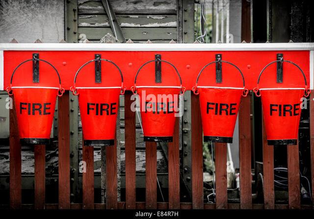 Five vintage firefighting buckets. - Stock Image