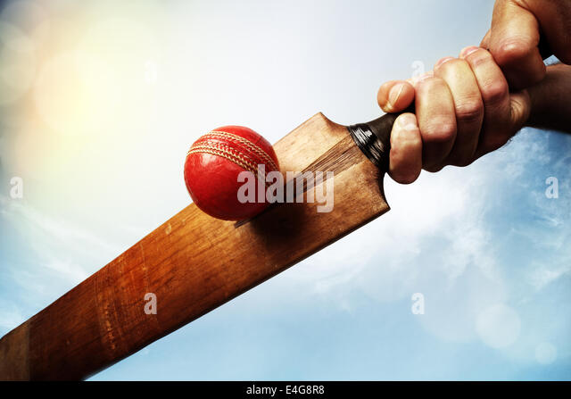 Cricket player hitting ball - Stock Image