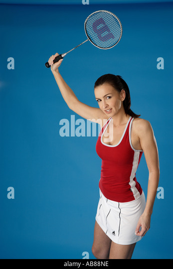 portrait of a young darkhaired woman in sport outfit with badminton racket - Stock Image
