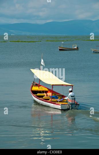 Man driving a tour boat after returning passengers at Lake Chapala, Mexico - Stock Image