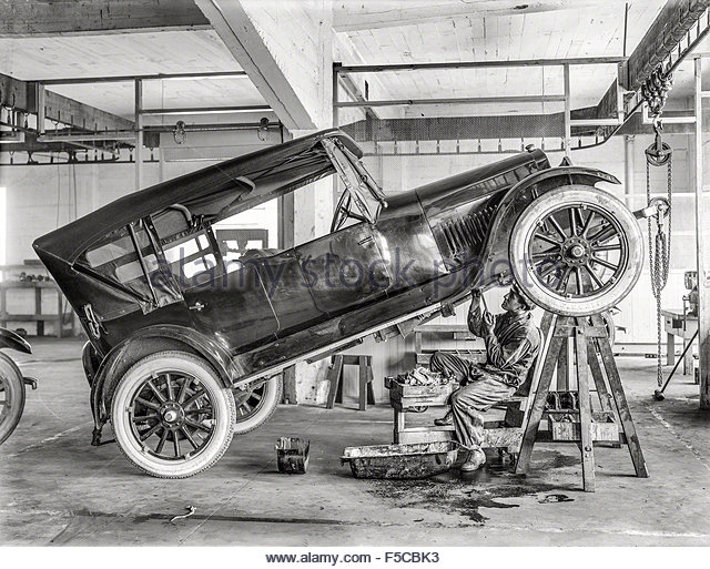 A vintage car at the garage and the mechanic working - Stock Image