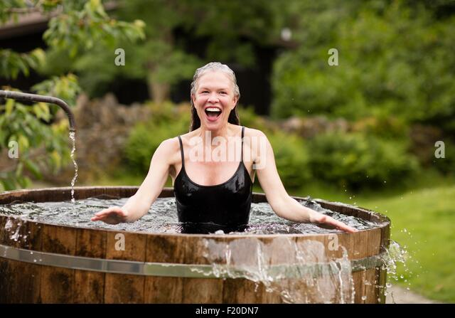 Mature woman standing in fresh cold water tub at eco retreat - Stock Image