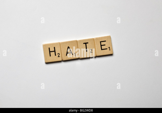 scrabble stones spelled hate - Stock Image