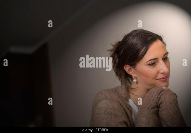 Close-up of a mid adult woman thinking with leaning on elbows, Munich, Bavaria, Germany - Stock-Bilder