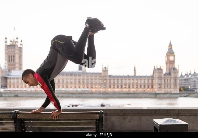 Young man leaping over park bench on Southbank, London, UK - Stock Image
