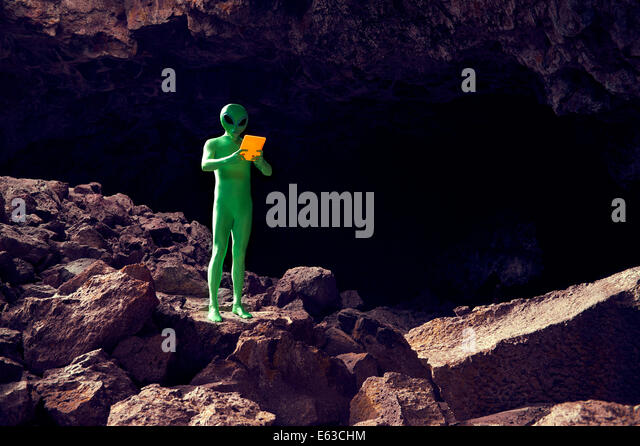 Explorer alien in dramatic cave landscape using futuristic technology glowing tablet - Stock Image